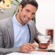 Businessmworking in his kitchen with cup of coffee — Stock Photo #8329637