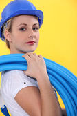 Female electrician carrying coil — Stock Photo