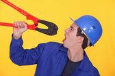 Mann hält einen bolzenschneider — Stockfoto