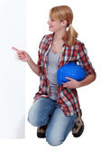 Kneeling tradeswoman pointing sideways — Stock Photo