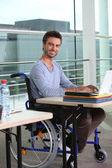 Man on laptop in wheelchair — Stock Photo