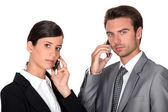 Executive couple using cellphones — Stock Photo