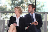 Business executives sitting on a bench texting — Stock Photo