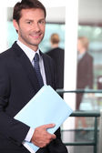 Businessman holding a file with colleagues out of focus in the background — Stock Photo
