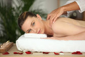 Young woman enjoying a rose scented back massage — Stock Photo