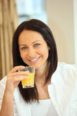 Thirty-ish brunette drinking orange juice — Stock Photo