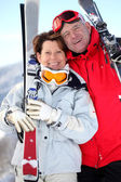 Older couple with skis — Stock Photo