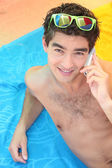 Young man lying on the beach with a cellphone — Foto Stock