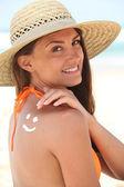 Frau mit sonnenschutz am strand trägt einen hut — Stockfoto
