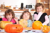 Giggling girls carving pumpkins — Stock Photo