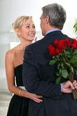 Uroczy pan ukrywanie róże za jego plecami — Zdjęcie stockowe