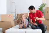 Couple lying on an unmade sofa bed celebrating their new home with champagn — Stock Photo