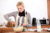Blonde woman making a cake — Stock Photo