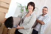 Couple with rolled up carpet surrounded by boxes — Stock Photo