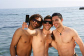 Young men taking pictures at the beach — Stock Photo