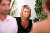 Woman in a black dress sitting in a restaurant — Stock Photo