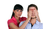 Woman putting her hands on man eyes — Foto Stock