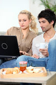 Couple with laptop having breakfast — Stock Photo