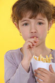 Little girl eating French fries — Stock Photo