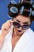 Woman with curler wearing bath robe and sunglasses — Stock Photo