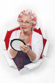 Old woman in rollers putting on lipstick — Stock Photo