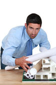 Young architect bending over desk with blueprints and model — Stock Photo