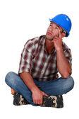 Pensive laborer sitting on white background — Stock Photo