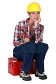 A female worker sitting on her toolbox. — Stock Photo