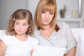 Unimpressed little girl with her mother and a laptop — Stock Photo