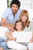 Parents and daughter with laptop computer — Stock Photo