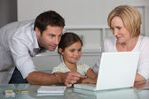 Parents and daughter on laptop — Stock Photo