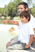 Father and son sitting by a lake — Stock Photo