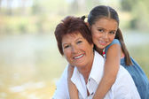 Young girl riding piggy-back on her grandmother's back — Stock Photo