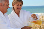 Mature couple drinking on beach — Stock Photo