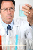 Male scientist holding glass beaker — Stock Photo