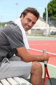 Tenista sedí na lavičce — Stock fotografie