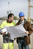 Travailleurs de la construction en regardant les plans de site — Photo