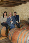 Three wine producers smiling in cellar — Stock Photo