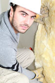 Man pushing wall insulation into place — Stock Photo