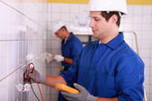 Two young electricians at work in a tiled room — Stock Photo