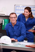 Workers looking up parts on the internet — Stock Photo