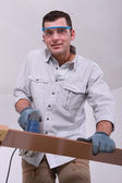Man cutting a floorboard — Stock Photo