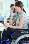 Young woman in a wheelchair at her desk — Stock Photo