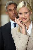 Młoda kobieta uśmiechając się z telefonu w dłoni — Zdjęcie stockowe