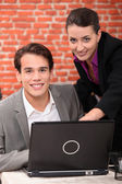 Couple using a laptop in a restaurant — Stock Photo