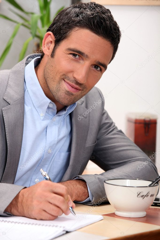 Charming 30 years old man dressed in a grey suit and writing in a cosy place — Stock Photo #8329581