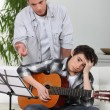 A father teaching his son how to play guitar. — Stock Photo