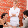 A couple dining at a restaurant and a waitress crossing her arms — Stock Photo #8330193