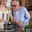 Young woman cooking for an elderly lady — Stock Photo