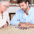 Young man playing game with elderly woman — Stock Photo #8331089
